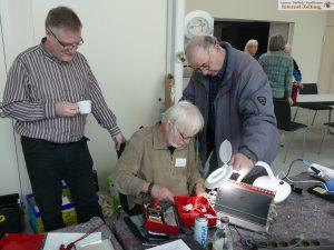 Pfarrer Jörg Geissler (l) beobachtet Franz Schulz bei der Reperatur eines Toasters